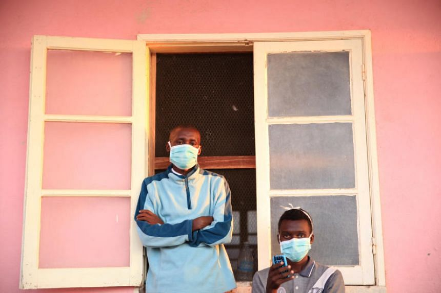 Tuberculosis patients, wearing masks to stop the spread of the disease, stand outside their ward at Chiulo Hospital, Cunene province, Angola, on Feb 22, 2018.