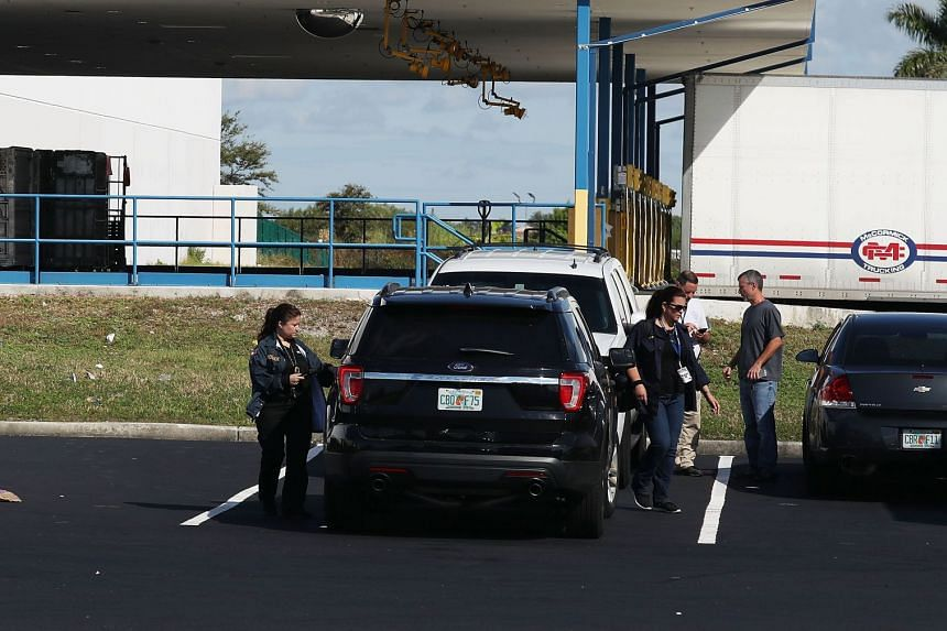 US postal workers are seen at a mail facility in Florida where federal law enforcement personnel were investigating the pipe bombs.