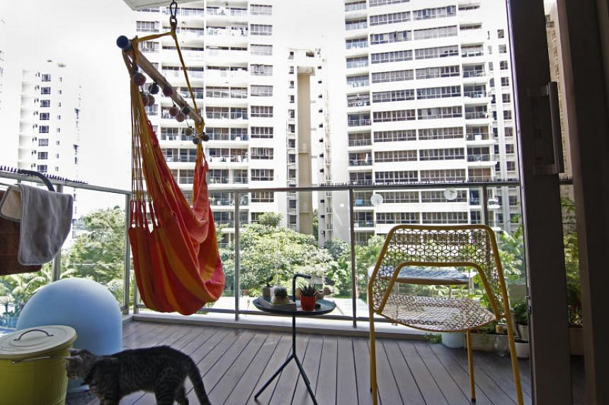 Ms Tay Ying Hui's balcony, where  she has managed to fit a sitting hammock, a small coffee table and chair, a herb garden and a hanging bed for the family's pet cat.