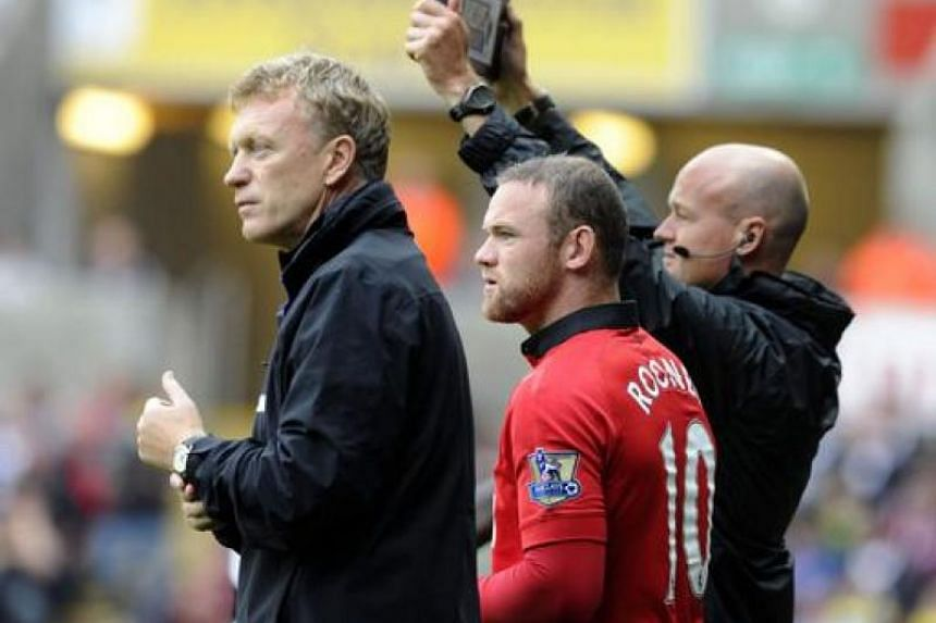 Manchester United's manager David Moyes (left) with Wayne Rooney, who is going on the pitch as a substitute against Swansea City, during their EPL match at Liberty Stadium, Swansea, on Aug 17, 2013.