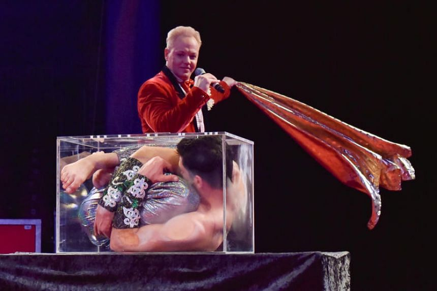 The Ringmaster, Stanislav Knyazkov, unveils a cloth to reveal Emin Abdullaev, 25, a contortionist in The Man In The Glass Box act.
