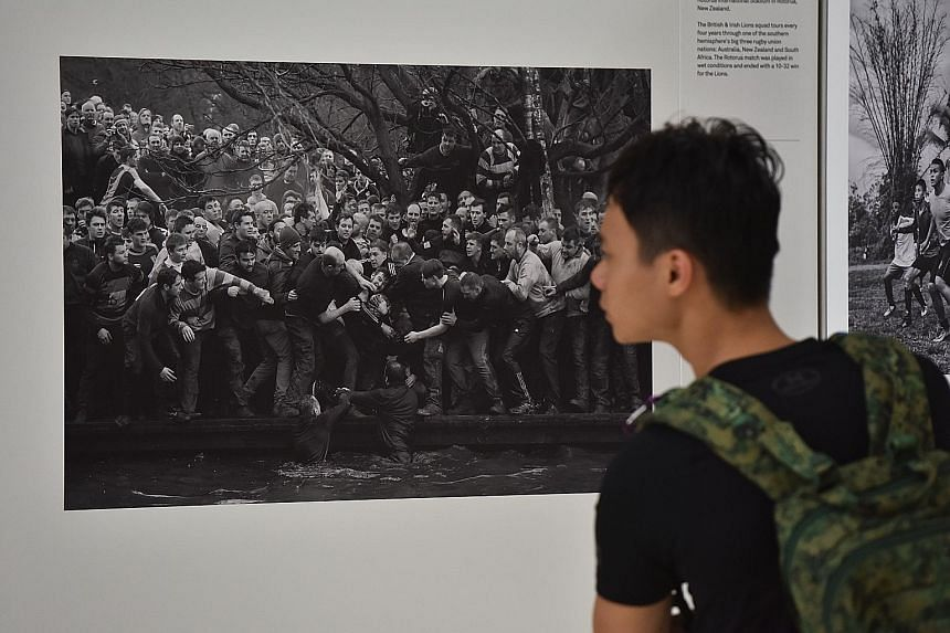 A photograph of the Royal Shrovetide Football match - an annual rugby-football hybrid game in Ashbourne, England - on display at the World Press Photo Exhibition at the National Museum of Singapore. The collection of pictures by 42 photographers from
