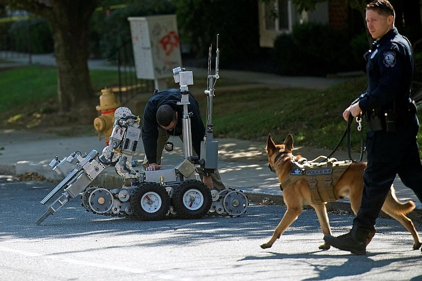 Police officers with a bomb disposal robot outside an evacuated post office in Wilmington, Delaware, on Thursday, after the discovery of additional suspicious packages. Two of them were intended for former vice-president Joe Biden in his home state o