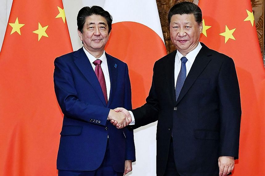 """Japanese Prime Minister Shinzo Abe (left) and Chinese President Xi Jinping meeting in Beijing yesterday. A Japanese government spokesman said Mr Xi will """"seriously consider"""" an invitation by Mr Abe to visit Tokyo."""