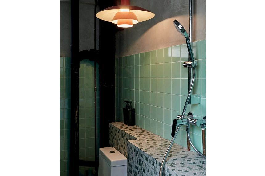 In a bedroom, wiring is concealed in metal piping and turned into a design feature. The bathroom (above) features partially tiled walls to mimic the cost-saving style favoured by builders in the 1960s.
