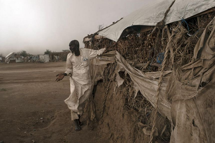 With a storm approaching, a man hurries to secure his shelter at a camp for displaced people in Bani Hassan, Yemen, on Oct 18, 2018.