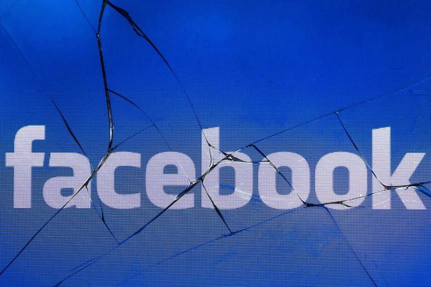 The logo of the social network Facebook on a broken screen of a mobile phone.