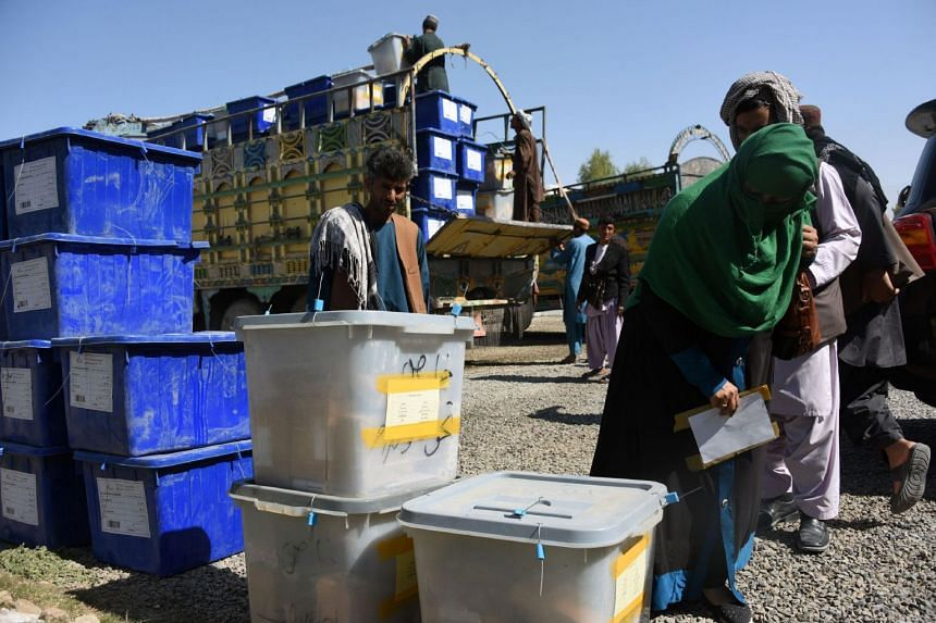 Afghan employees of the Independent Election Commission unload ballot boxes from a truck at a polling centre ahead of a legislative election in Kandahar on Oct 26, 2018.