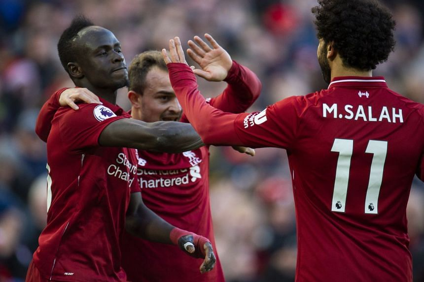 Liverpool's Mohamed Salah (L) is congratulated by his team mates after scoring.
