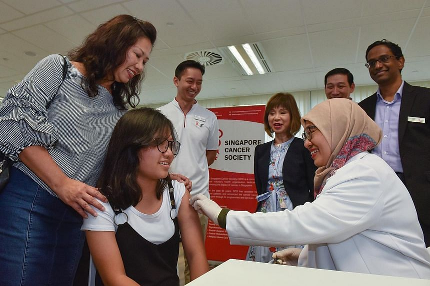 Chloee Lee receiving her HPV vaccination yesterday from Dr Hafidza Mohd Said, with encouragement from her mother, Madam Dianna Tan. Behind them are (from left): Mr Melvin Seet, senior manager of community health, Singapore Cancer Society (SCS); Dr Am