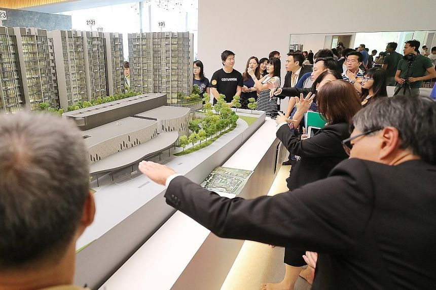 People viewing a model of The Woodleigh Residences at the soft launch yesterday. Sales for the mixed-use commercial and residential development have not begun and visitors to the showroom said they were keen to return when sales start on Nov 10.