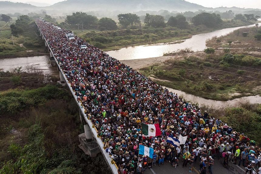 Honduran migrants heading in a caravan to the US as they leave Arriaga in southern Mexico yesterday on their way to San Pedro Tapanatepec. A Central American migrant washing himself in the Suchiate River yesterday in Tecun Uman, Guatemala. Far left:
