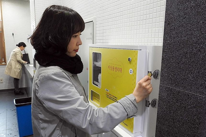 A Seoul government official inserts a gold coin into a dispenser to get a free sanitary pad inside a toilet at the Seoul Metropolitan Library. Concerns about the public abusing the free service were unfounded, judging from the number of pads taken.