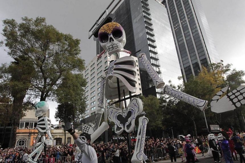 People participate in a parade held to commemorate the traditional 'Day of the Dead' in Mexico City, on Oct 27, 2018.