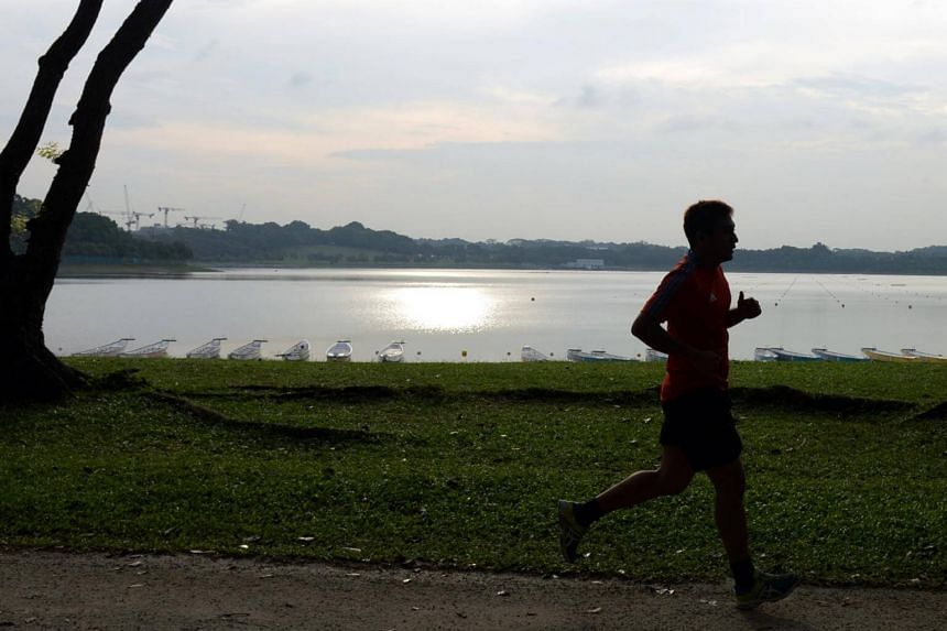 File photo of a man jogging along Bedok Reservoir. Exercise may be beneficial when one is suffering from an upper respiratory tract infection, also known as the common cold.