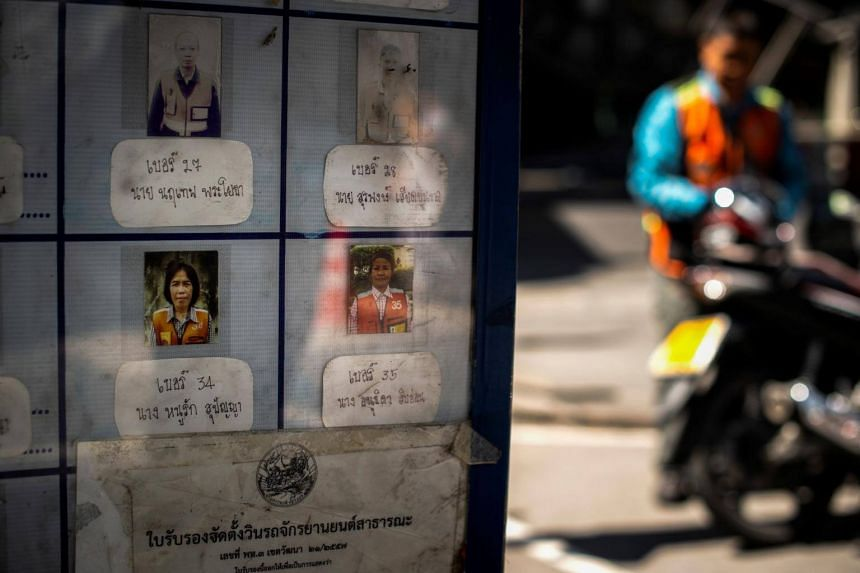 Pictures of two female motorcycle-taxi drivers on an identification board at a motorcycle-taxi stand in Bangkok.