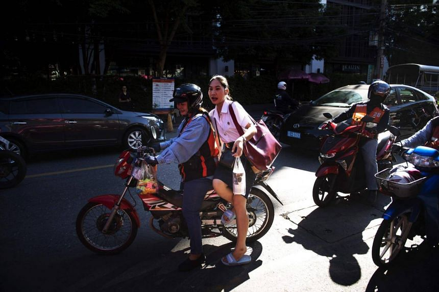 """A female motorcycle-taxi driver, locally known as """"motorsai"""", picking up a passenger in Bangkok."""