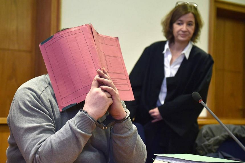 Former male nurse Niels Hoegel hides his face behind a folder as he waits next to his lawyer Ulrike Baumann on Feb 26, 2015.