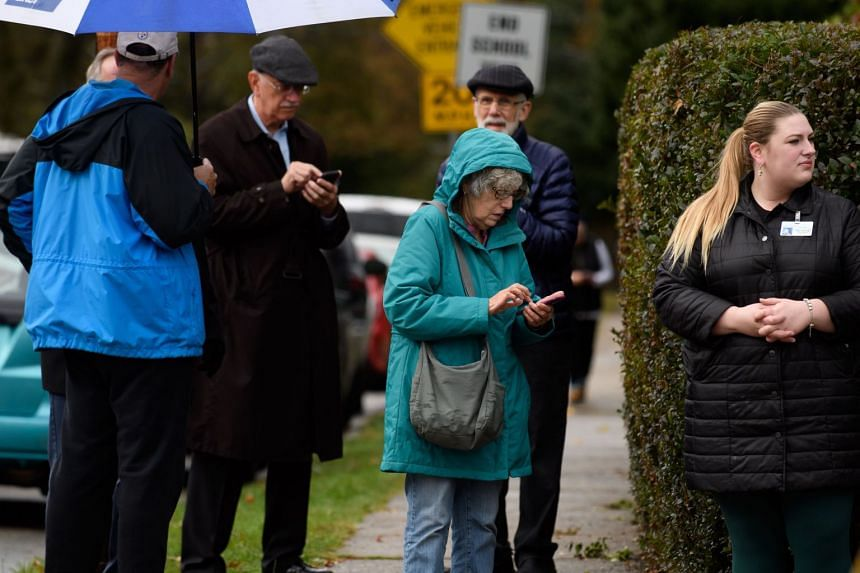 Residents check their phones near the site of the mass shooting.