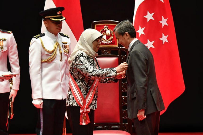 President Halimah Yacob giving the Meritorious Service Medal to National Gallery Singapore chairman Hsieh Fu Hua on Oct 28, 2018.