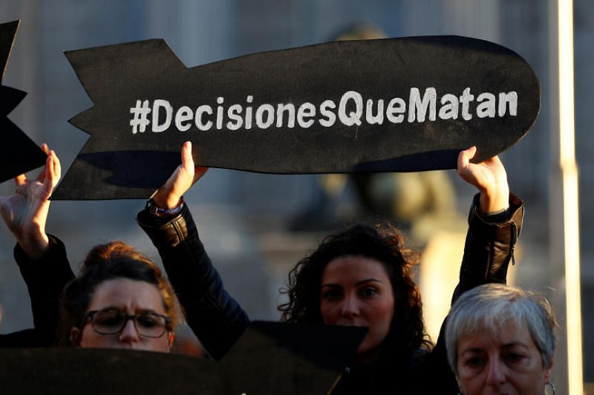 """A protester holding a placard that says """"Decisions that kill"""" during a demonstration to demand the halting of arms sales to Saudi Arabia, in Madrid on Oct 24, 2018."""