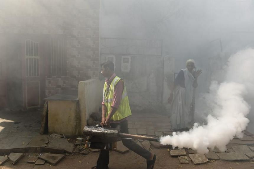 An Indian worker from Ahmedabad Municipal Corporation fumigating an area to prevent mosquitoes from breeding in a residential colony in Ahmedabad, Gujarat state, on Oct 27, 2018.