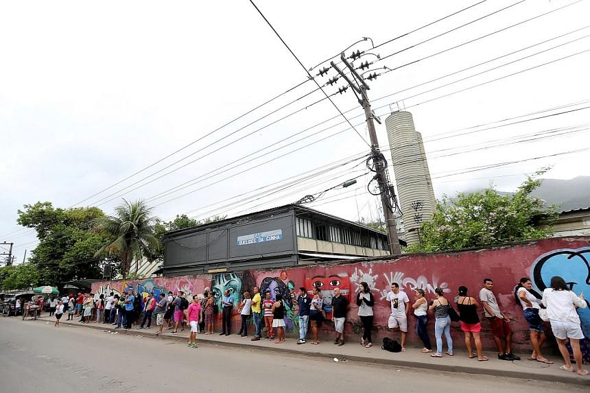 Brazilians standing in line outside a polling station to cast their votes in a run-off election in Rio de Janeiro yesterday. Far-right candidate Jair Bolsonaro, who has tapped anti-establishment anger but also repulsed part of the electorate with den
