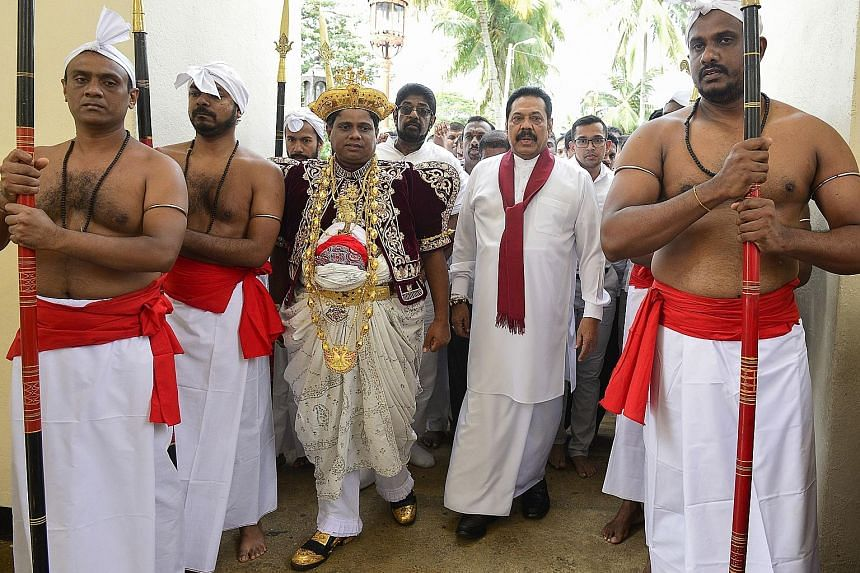 Mr Ranil Wickremesinghe (above) has declared his dismissal illegal and refused to vacate the prime minister's official residence. Former strongman Mahinda Rajapaksa (right, with red scarf), seen here arriving at the Temple of the Sacred Tooth Relic i