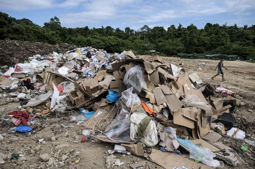 A child walks past rubbish at the materials recovery facility dumpsite on the Philippine island of Boracay, on Oct 27, 2018.
