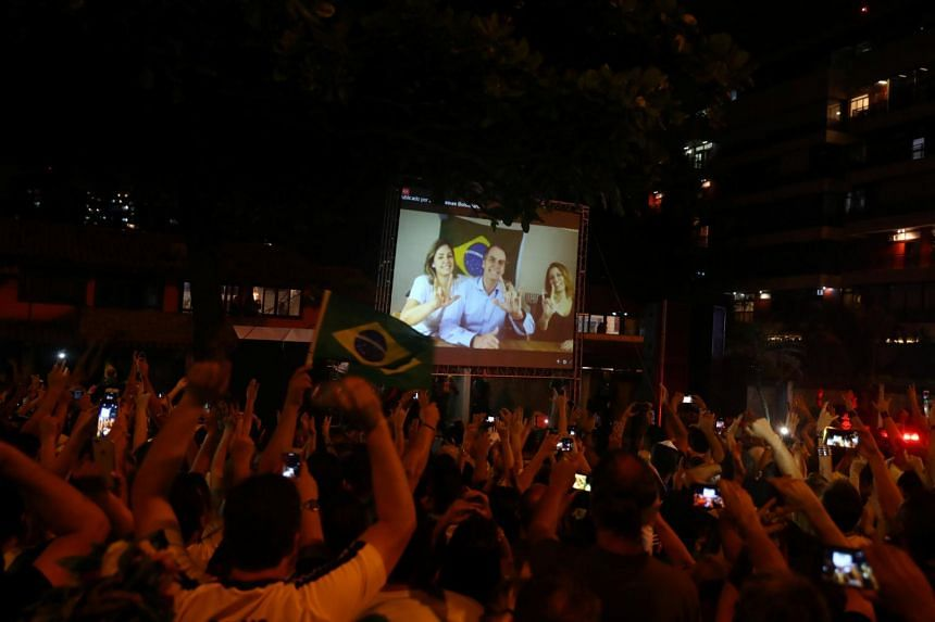 Supporters of Jair Bolsonaro react while watching him on a screen, after he won the presidential race, in Rio de Janeiro, Brazil, on Oct 28, 2018.