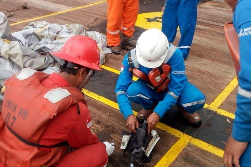 Personnel from Pertamina Hulu Energi Offshore North West Java, a subsidiary of state owned oil company Pertamina, checking the debris recovered from the site.