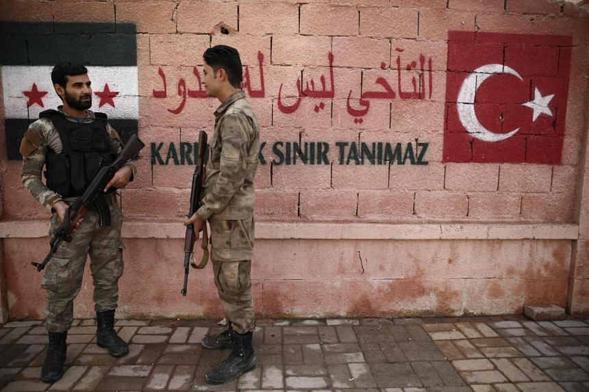 Turkish-backed Syrian police stand guard outside the Local Council building in the northern city of Azaz in the rebel-held region of Aleppo, near the border with Turkey, on Oct 16, 2018.