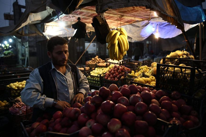 A Syrian man stands at his vegetable stall in the northern city of Azaz in the rebel-held region of Aleppo, near the border with Turkey, on Oct 16, 2018.