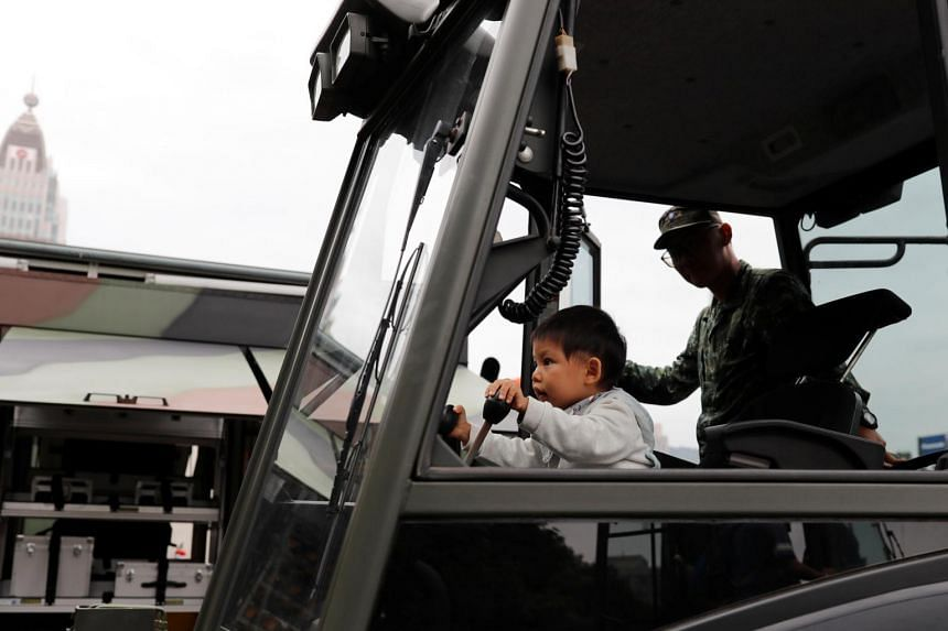 A child sits inside a military vehicle during a public fair which displays military equipments, in Taipei, on Sept 29, 2018.
