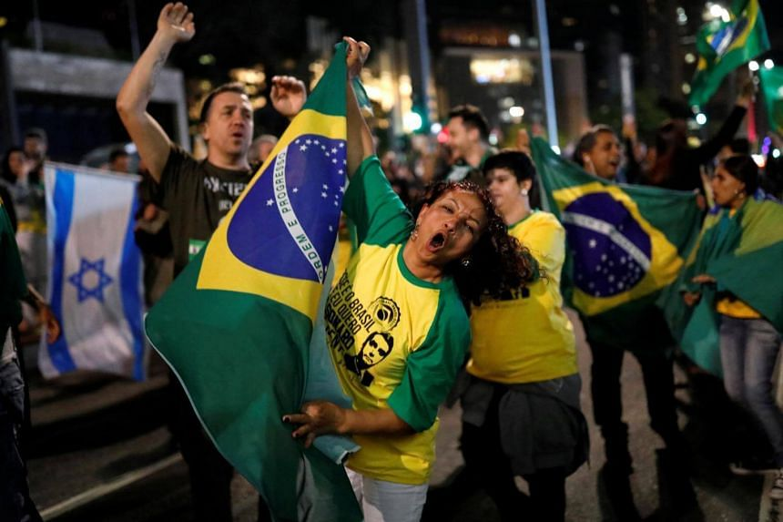 Supporters of Jair Bolsonaro react after polls closed, in Sao Paulo, Brazil, on Oct 28, 2018.