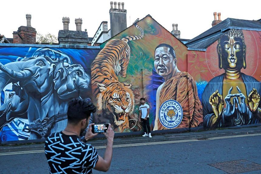 Visitors take photos in front of a mural representing Leicester City owner Vichai Srivaddhanaprabha, on Oct 28, 2018.