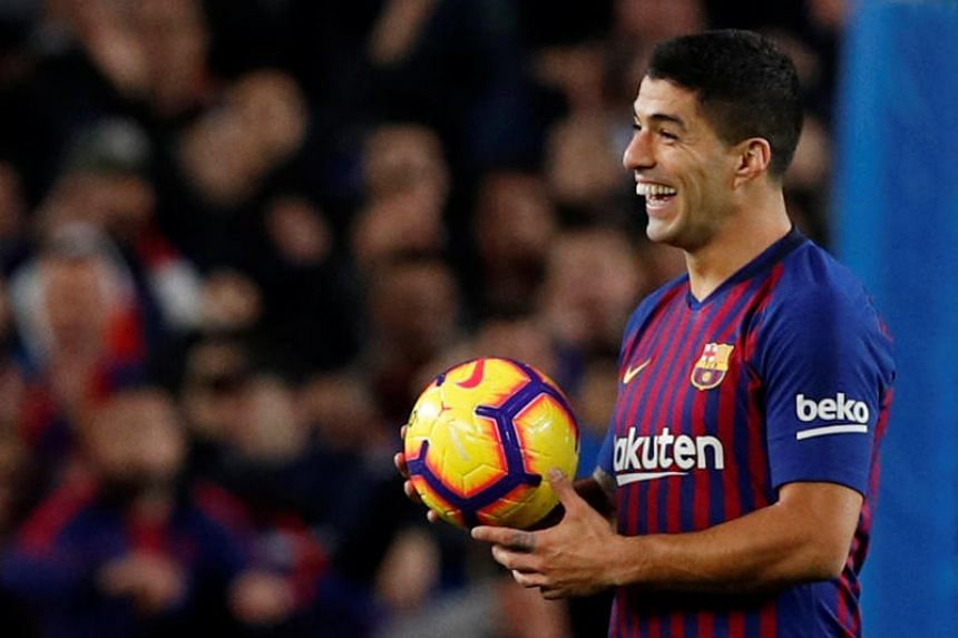 Barcelona's Luis Suarez celebrates at the end of the match with the ball after completing his hat-trick at the Camp Nou, Barcelona, Spain, on Oct 28, 2018.