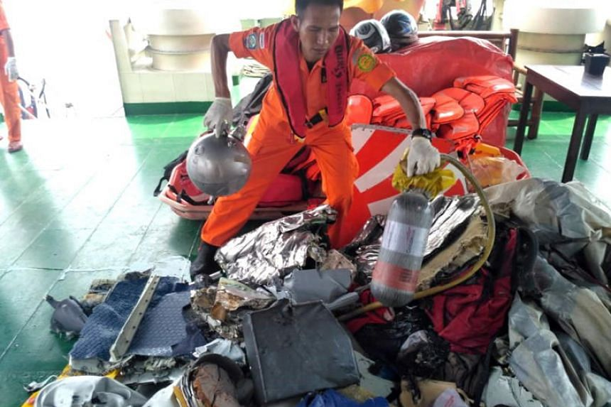 An Indonesian rescuer evacuating parts from a crashed Lion Air passenger plane in waters off Tanjung Karawang, West Java, Indonesia.