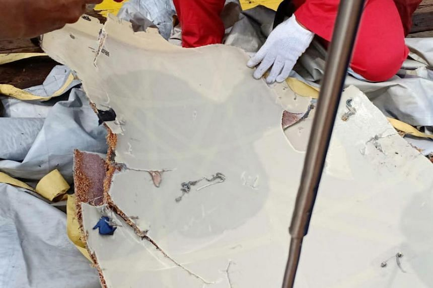 PT Pertamina workers examine recovered debris believed to be from the crashed Lion Air flight JT610.