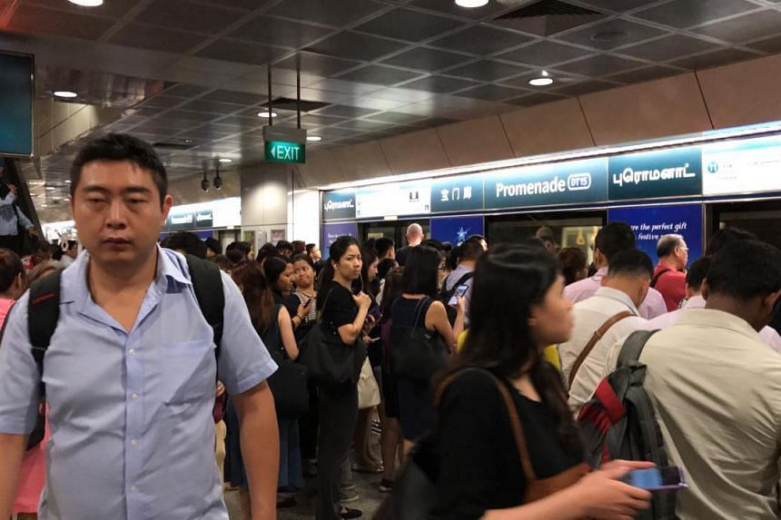 Commuters waiting at the Promenade MRT station after a train fault delayed service along the Downtown Line during the evening peak period evening on Oct 29, 2018.
