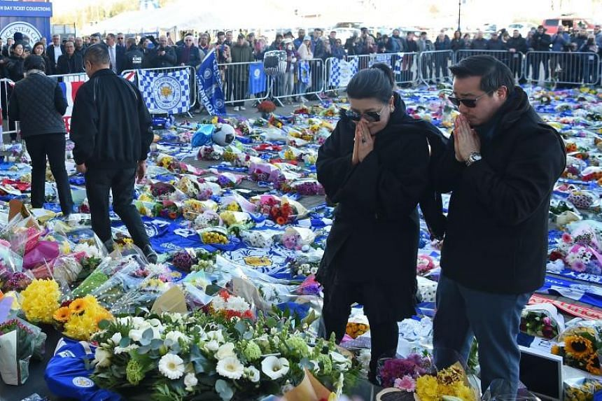 Aimon (second from right) and Khun Aiyawatt Srivaddhanaprabha (right), the wife and son of Vichai Srivaddhanaprabha, joined hundreds of fans at King Power stadium where a mass of messages, floral tributes, shirts and scarves were laid in honour of th