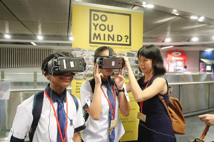 (From left) Hougang Secondary School students Malabanan Ace Brendan Malones and Phoebe Teo trying the Virtual Reality Immersive Experience on depression with help from teacher Madeline Neo at HarbourFront MRT station.