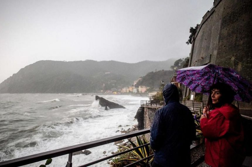 People stand at the shore of the rough sea in Monterosso al Mare, village in the Liguria region, on Oct 29, 2018.