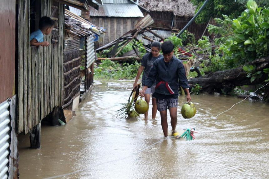 Villagers walk on a flooded path in the typhoon-hit town of Casiguran in the Philippines' Aurora province on Oct 30, 2018.