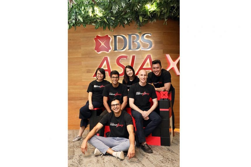 impress.ai chief executive Sudhanshu Ahuja (back row, second from left) and Every Botty chief executive Shane Kelly (second from right) with members from DBS' Innovation Group, led by Mr Bidyut Dumra (seated on the ground).