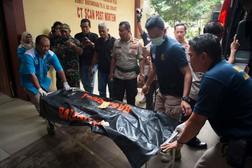 Forensic police receive a body bag containing the remains of a passenger of the crashed Lion Air flight JT610 outside the police hospital morgue in Jakarta on Oct 30, 2018.