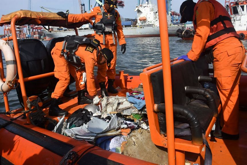 Indonesian rescue team members collect debris of Lion Air flight JT610, that crashed into the sea, at Tanjung Priok port in Jakarta, on Oct 29, 2018.