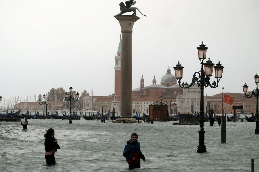 People wade through flooded St Mark's Square during a period of seasonal high water in Venice, Italy, on Oct 29, 2018.