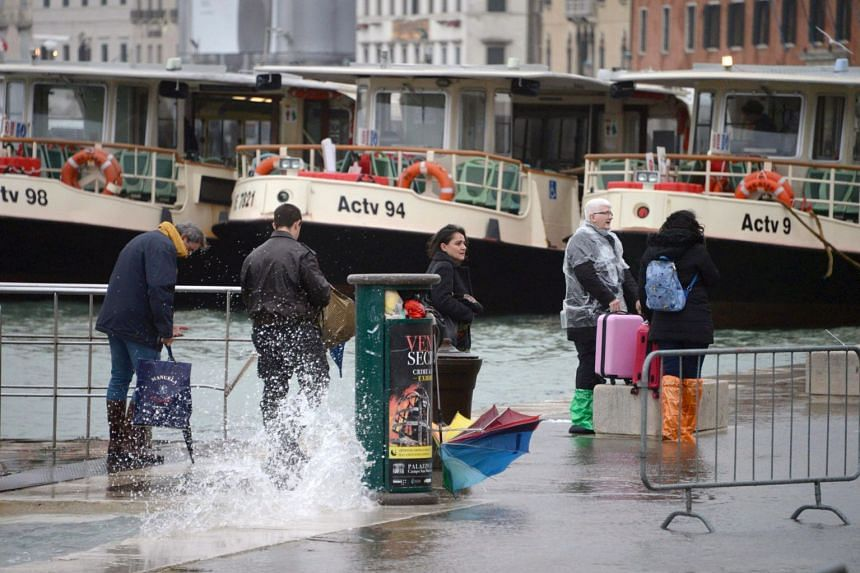 Tourists wander in high water in Venice, Italy, on Oct 29, 2018.