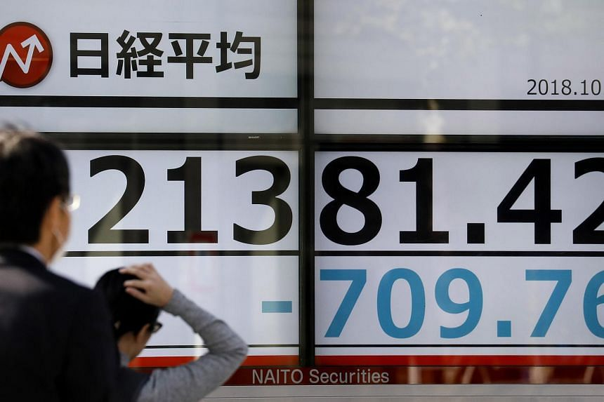 Tokyo businessmen walk past a display showing Tokyo's Nikkei Stock Average during an afternoon trade session in Tokyo, Japan, on Oct 25, 2018.